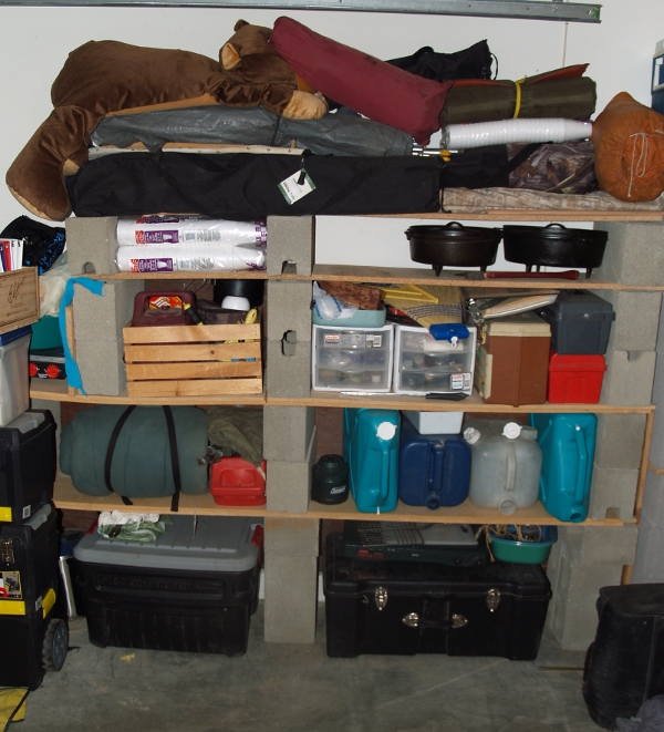 home made shelving to store camp gear on made out of planks of wood and bricks