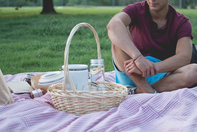 A guy sitting on a picnic blanket